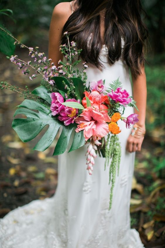 a bright tropical beach wedding bouquet of a monstera leaf, coral and hot pink blooms plus greenery