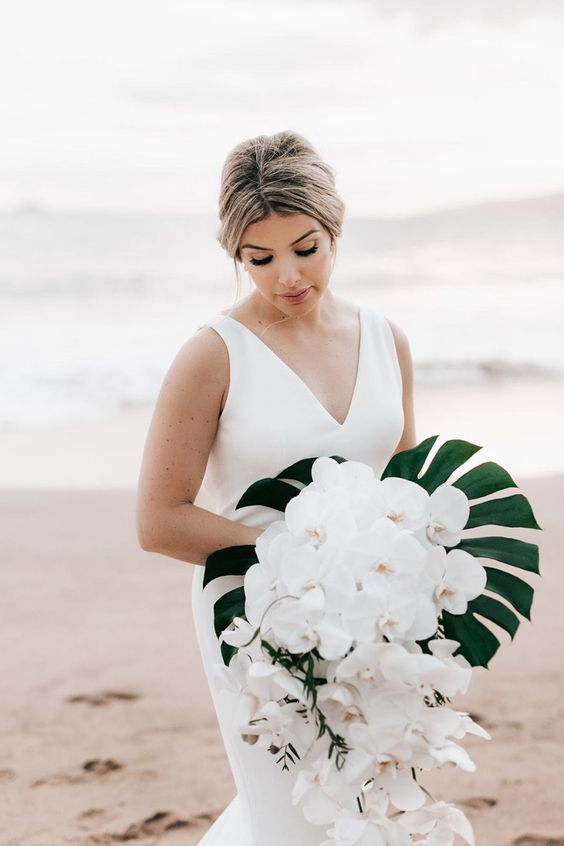 a cascading beach wedding bouquet of a large monstera leaf and white orchids going down