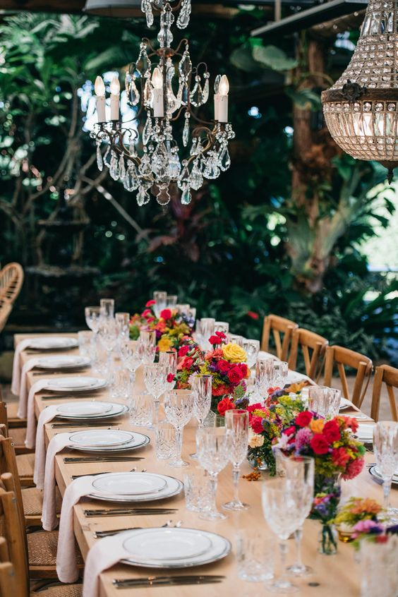 a chic and refined summer wedding tablescape with bold blooms, crystal chandeliers, neutral linens