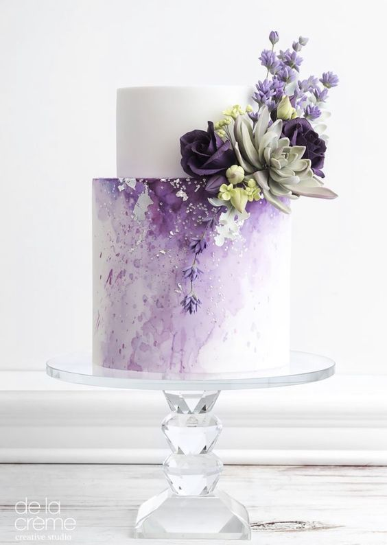 a chic lilac wedding cake with a white tier, an ombre effect, some succulents and sugar blooms