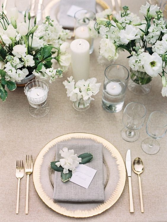 a chic neutral wedding tablescape with neutral linens, gold chargers and cutlery, neutral blooms and candles