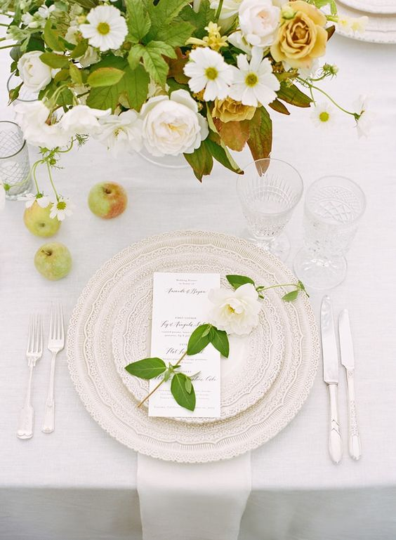 a chic summer wedding table with beautiful lace plates, neutral florals, apples and refined cutlery