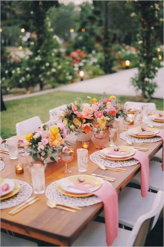 a chic summer wedding table with pink and yellow blooms, with pink napkins, yellow porcelain and gold touches