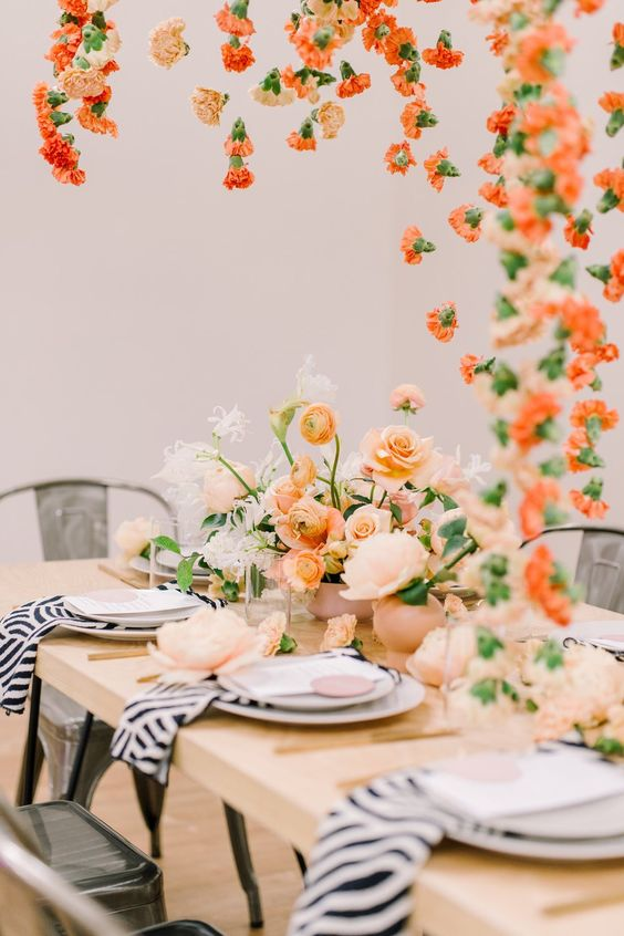 a chic summer wedding tablescape with pastel florals, with zebra print napkins, gold cutlery and lots of blooms hanging over the space