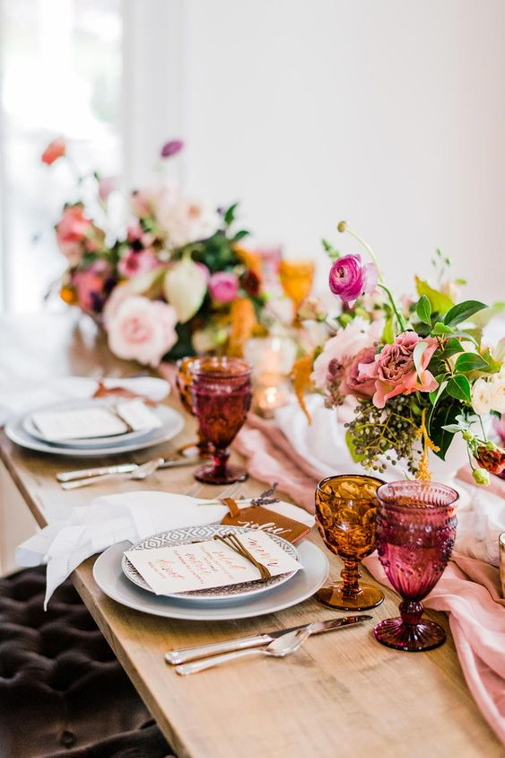 a chic summer wedding tablescape with printed plates, elegant pink blooms, pink and amber glasses and silver cutlery