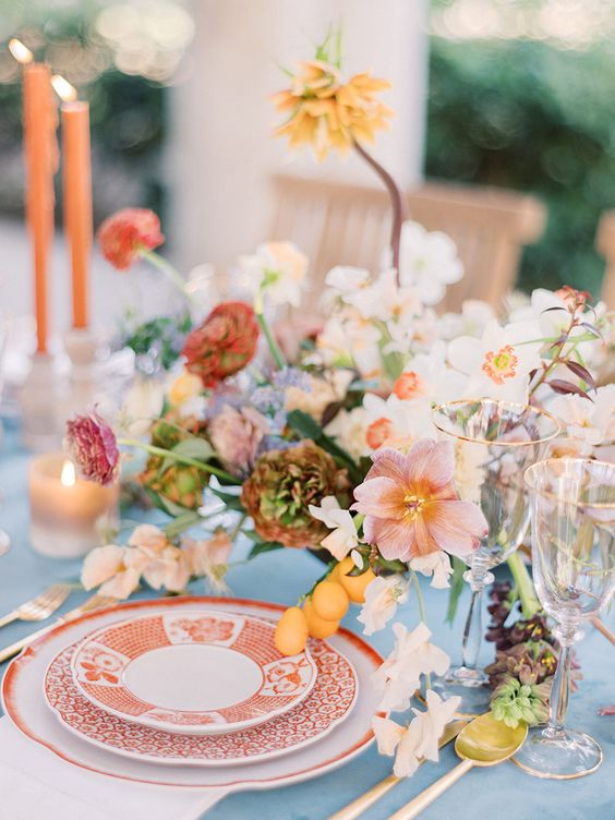 a chic summer wedding tablescape with printed plates, refined florals, colorful candles and succulents