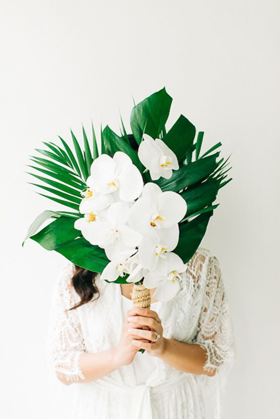 a chic tropical wedding bouquet of tropical leaves, white orchids and a lace wrap for a beach wedding