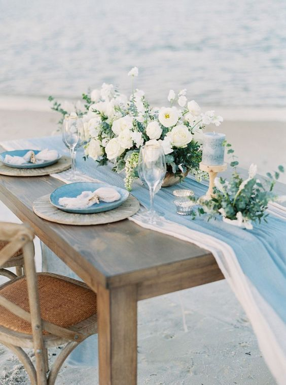 a coastal tablescape with two airy table runners, blue and neutral plates, blue candles and a neutral floral centerpiece