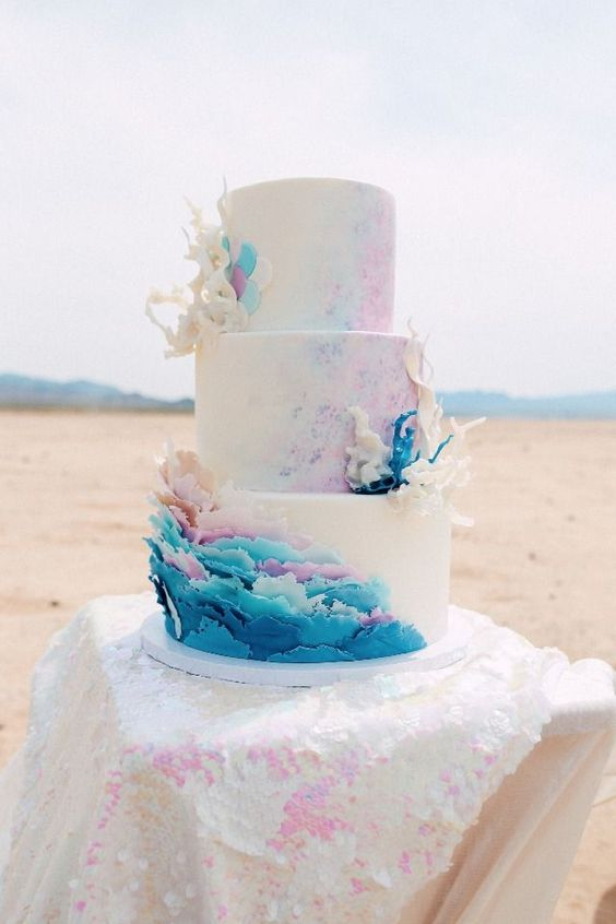 a colorful beach wedding cake with blue and pink watercolors, with colorful waves, corals and scales on the top tier
