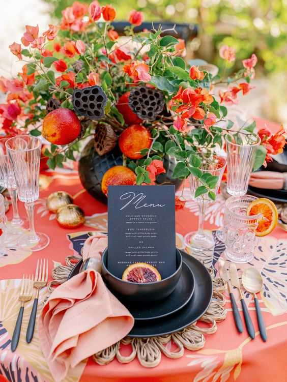 a colorful dramatic summer wedding table with a printed tablecloth, a super bold floral centerpiece with fruits, gold porcelain and cutlery