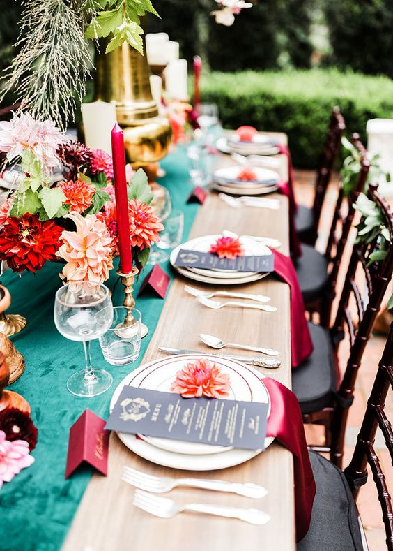 a colorful dramatic summer wedding tablescape with a turquoise runner, red candles and napkins and bright blooms
