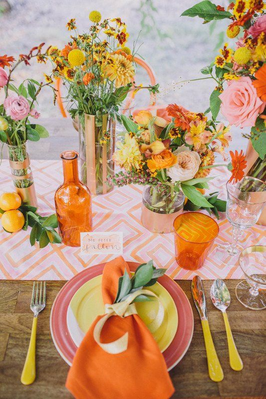 a colorful summer wedding tablescape with a printed table runner, bright blooms, glasses and neon cutlery, colorful plates