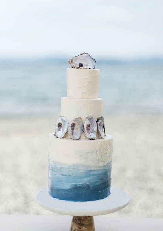 a creative ombre beach wedding cake with seashells and a black pearl is a lovely and chic idea to try