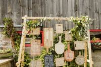 a creative rustic wedding seating chart done with cutting boards and greenery is a stylish barn idea