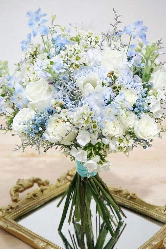 a dreamy wedding bouquet of light blue and white blooms plus a turquoise wrap is a cute idea