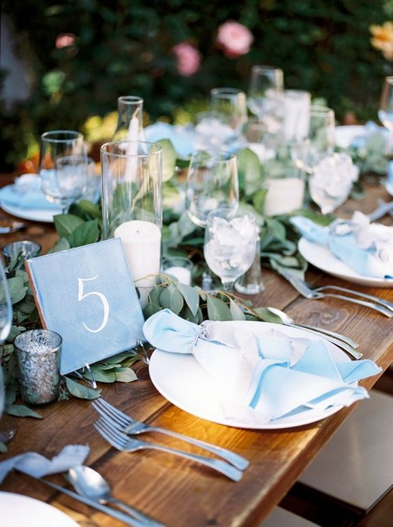 a fresh summer wedding tablescape with blue napkins, a tile table number, greenery and candles