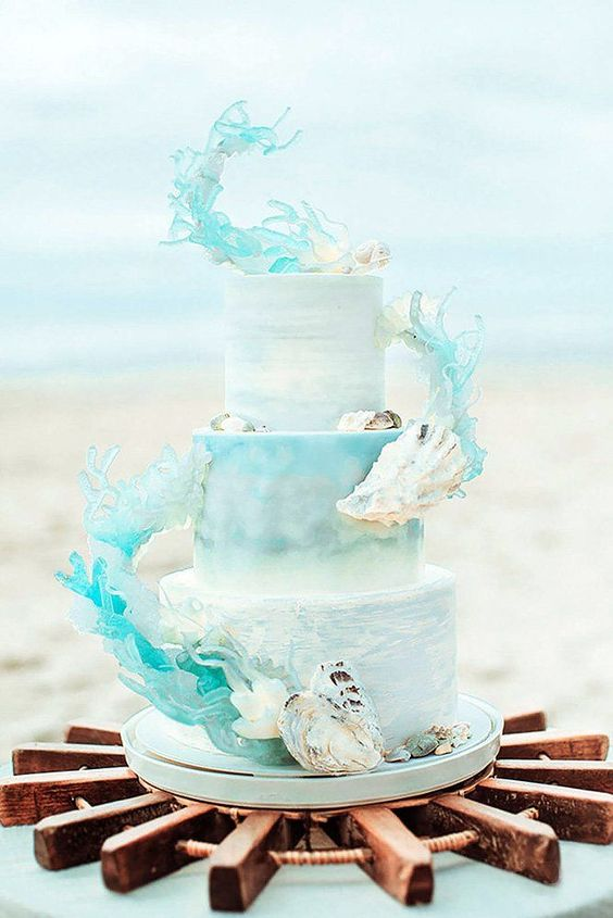 a light blue beach wedding cake with sugar seashells and waves attached looks very spectacular as if it's right out of the sea