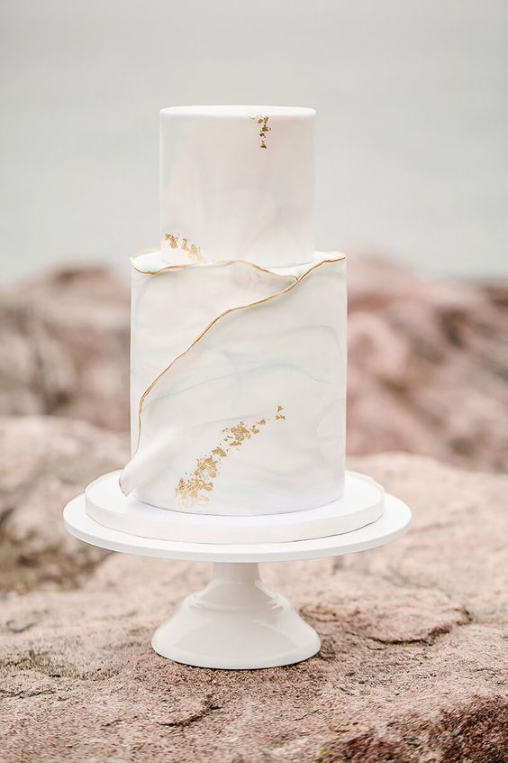 a light blue watercolor covered wedding cake with a gold edge and gold leaf is a very ethereal wedding idea