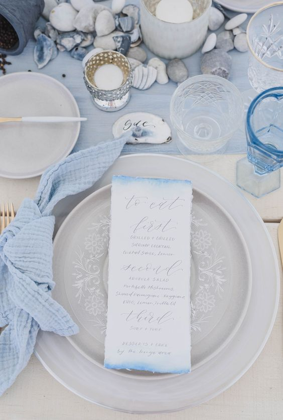 a light blue wedding table with a light blue runner, napkins, grey porcelain, various glass candle holders and pebbles plus seashells