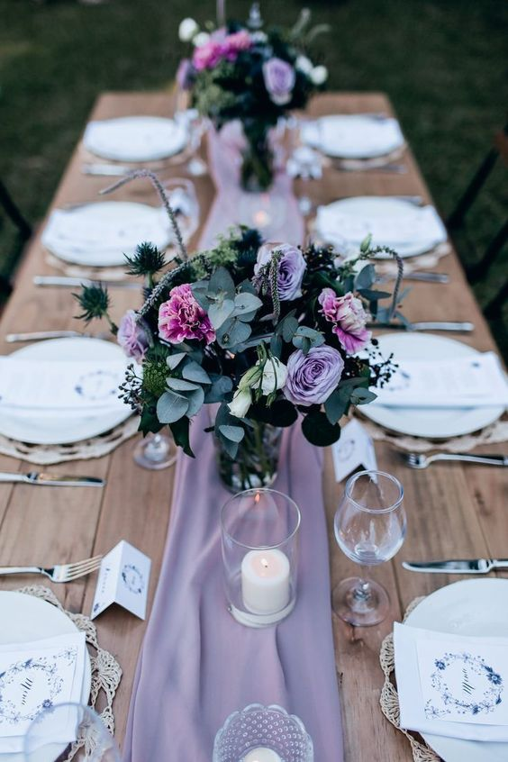 a lilac fabric runner, a bouquet of lilac and pink blooms plus greenery and thistles for a beautiful tablescape