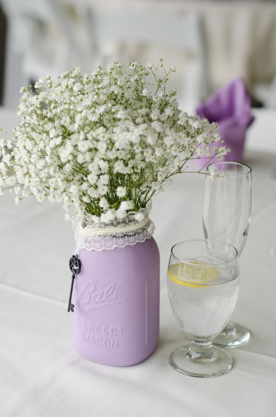 a lilac jar with a lace cover and baby's breath is a chic and beautiful wedding centerpiece
