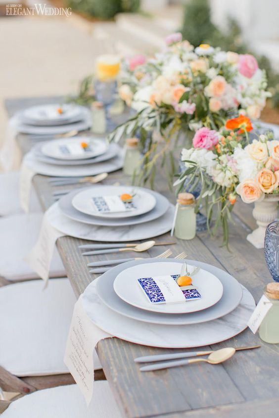 a lively summer wedding table with marble chargers, bright blooms, blue glasses and printed menus