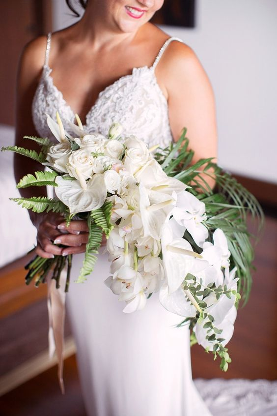 a luxurious cascading beach wedding bouquet of white roses and callas and greenery