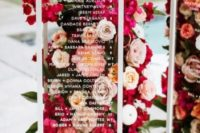 a modern seating chart with glass cubes and bright blooms and greenery is a cool idea for a floral-filled wedding