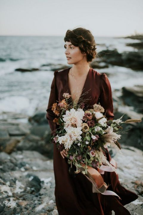 a moody textural wedding bouquet of fresh and dried blooms, dried foliage and herbs plus orange ribbons