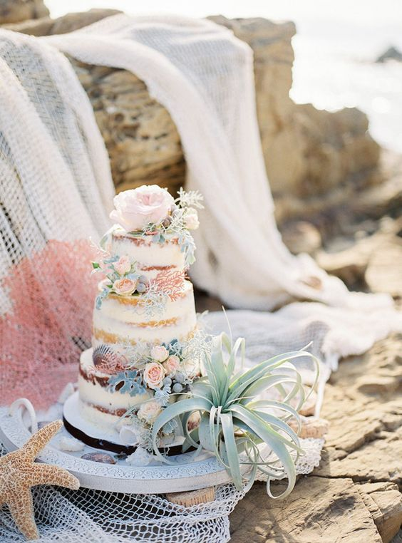 a naked beach wedding cake with blush blooms, pale greenery, seashells and an air plant is chic