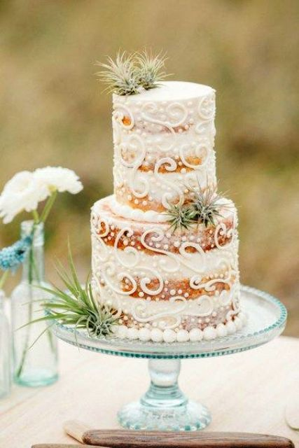 a naked patterned beach wedding cake with pearls and air plants is a lovely and chic dessert for a beach or coastal wedding