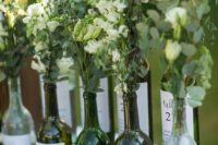 a natural wedding seatign chart with bottles and fresh greenery and white blooms plus a seating plan on them
