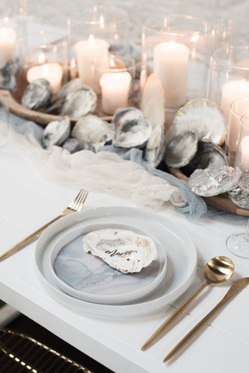 a neutral beach wedding tablescape with fabric runners, seashells, candles, watercolor porcelain and gold cutlery