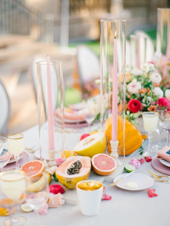 a pastel summer wedding tablescape with pink candles, lots of fruits on the table and bright blooms