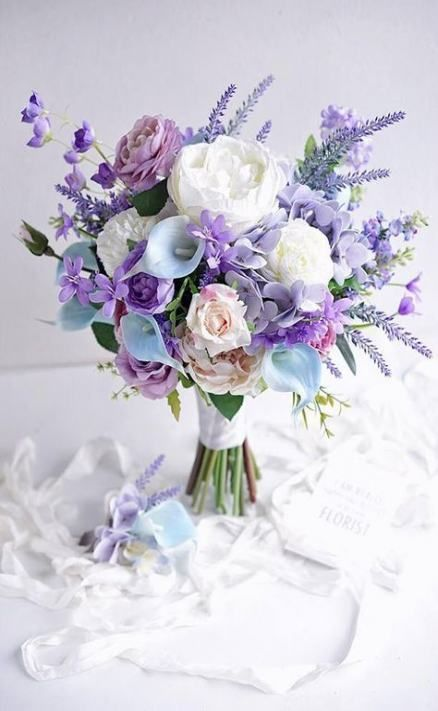 a pastel wedding bouquet with lilac, purple and blush and white blooms and some foliage