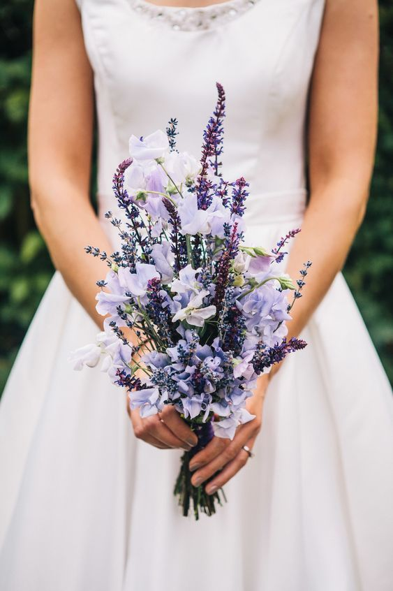 a purple and liac wedding bouquet with a unique shape is amazing for a summer bride or bridesmaid