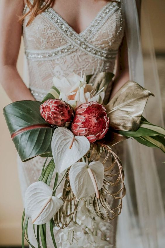 a quirky dimensional and textural wedding bouquet with green leaves, large pink blooms, touches of dried herbs