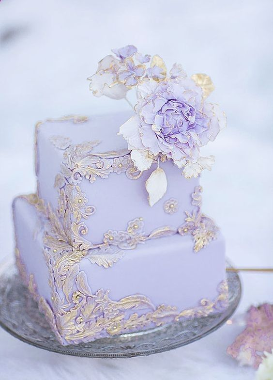a refined lilac wedding cake with chic 3D gold patterns and some matching sugar flowers on the top