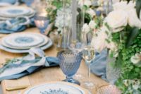 a refined summer wedding table in blues, with printed plates, white roses, greenery, blue candles and glasses
