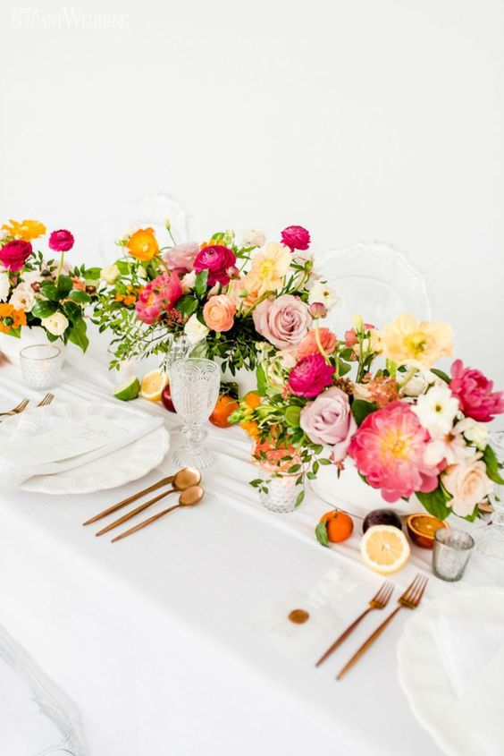 a refined summer wedding tablescape with super bright blooms and greenery, fruits, copper cultery and white plates