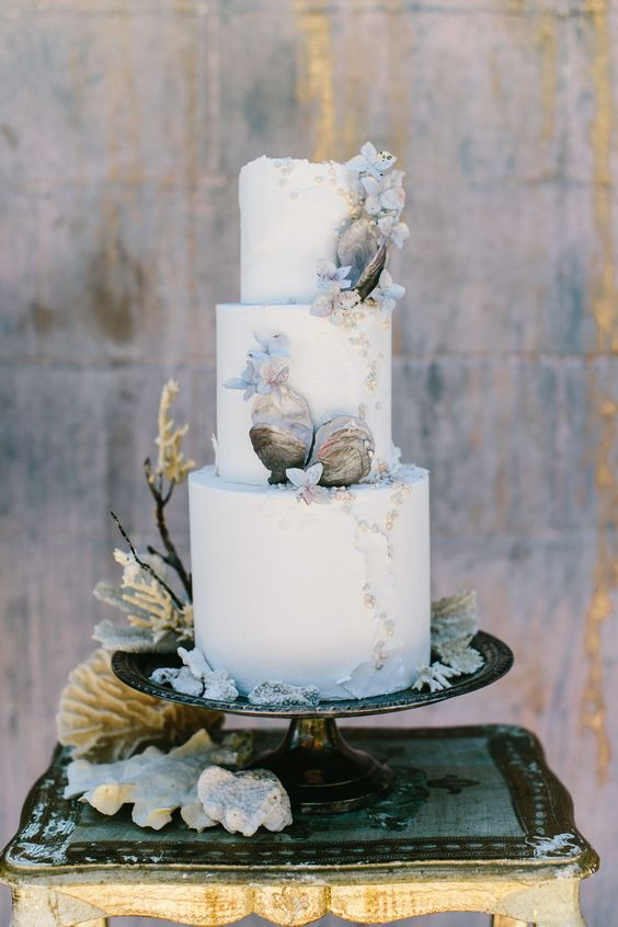 a refined white wedding cake decorated with pearls, blooms and seashells, all made of sugar and looking chic
