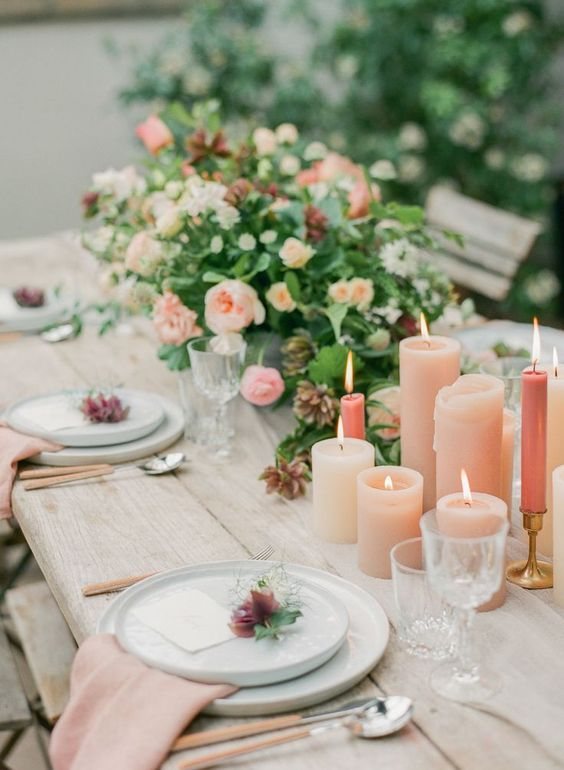 a romantic summer wedding table with blush candles, neutral plates, blush napkins and tender florals