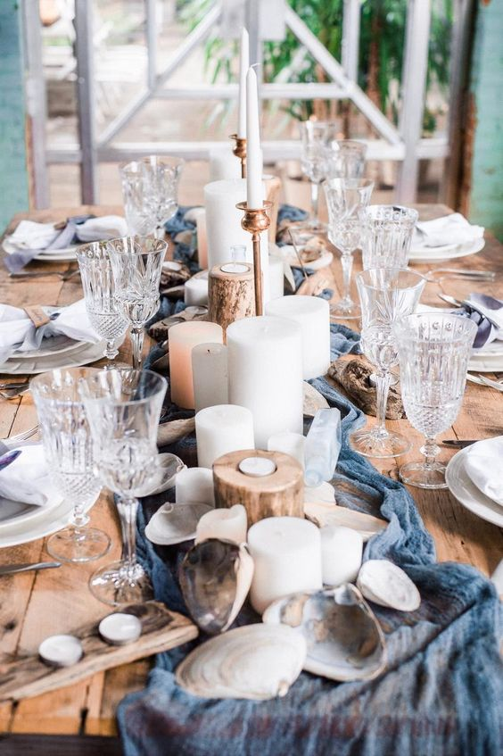 a rustic beach wedding table with a blue runner, pillar candles, wooden candleholders and seashells is a fresh take on traditions