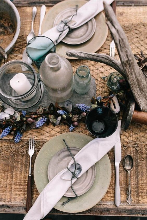 a rustic beach wedding table with grey and light green plates, driftwood, seashells, bottles and glass candleholders