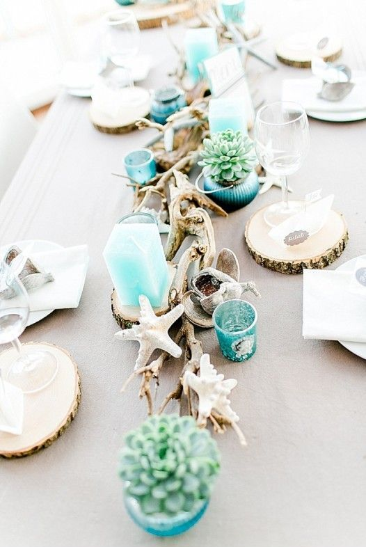 a rustic beach wedding tablescape with driftwood, starfish, bright turquoise candles and vases with succulents plus wood slice coasters