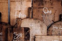 a rustic seating chart made of wooden cutting boards is a very cool idea that allows upcycling