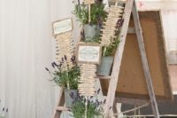 a rustic wedding seating chart done on wooden pegs, with lavender and signs is a chic idea