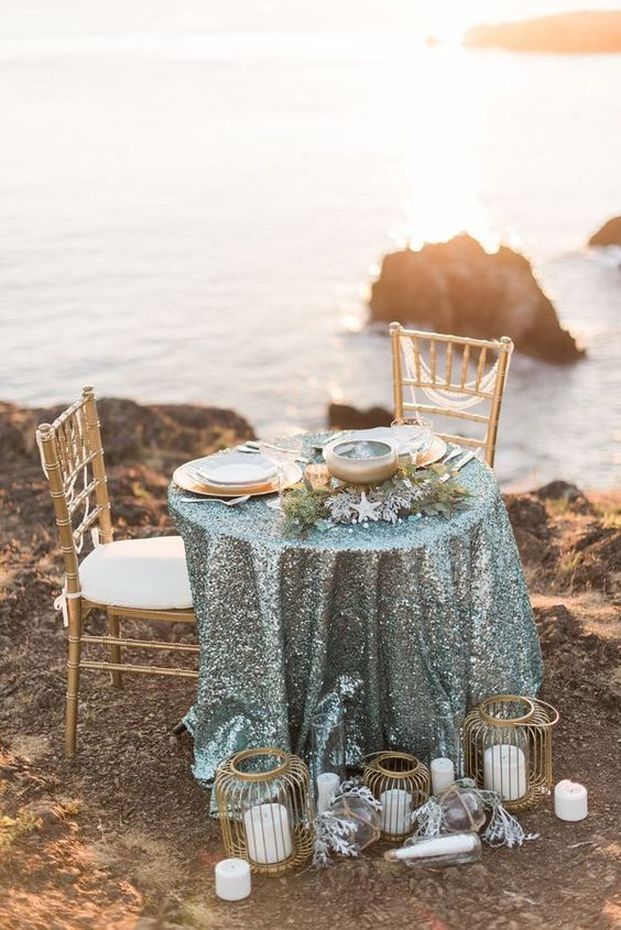 a sea glass colored sequin tablecloth, greenery, starfish and gold placemats plus gold candle lanterns and pillar candles