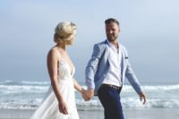 a sea-inspired groom's outfit with a light blue jacket, navy pants, a white shirt and no tie