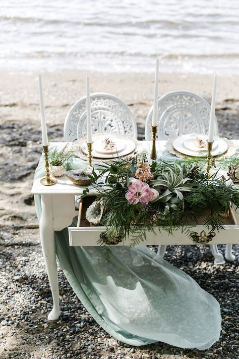 a seaglass colored tablescape with air plants, greenery, pink blooms, tall candles and an airy light green runner